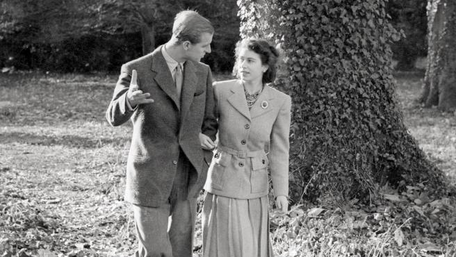 Isabel II y el duque de Edimburgo paseando por un parque, durante un reportaje cuando se comprometieron, en 1946.