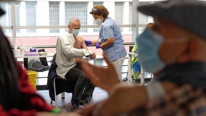 Varias personas reciben sus respectivas dosis de vacuna en el Wizink Center de Madrid.