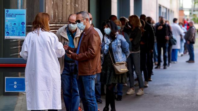 Varias personas hacen cola en el centro de vacunación UB Raval, en Cataluña.