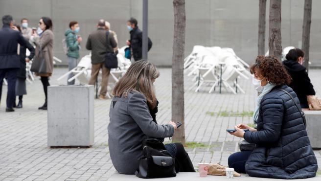 Varias personas consumen en la calle frente a unas terrazas cerradas en L'Hospitalet de Llobregat, en Barcelona.