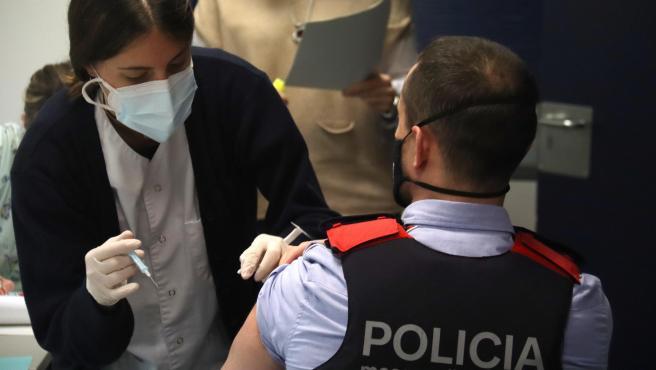 Una sanitaria administra la vacuna de la covid-19 a un agente de los Mossos d'Esquadra.