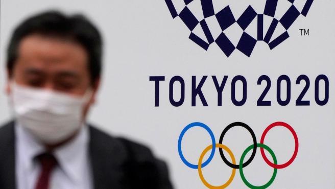 Un hombre con mascarilla pasea delante del logo de los Juegos Olímpicos de Tokio