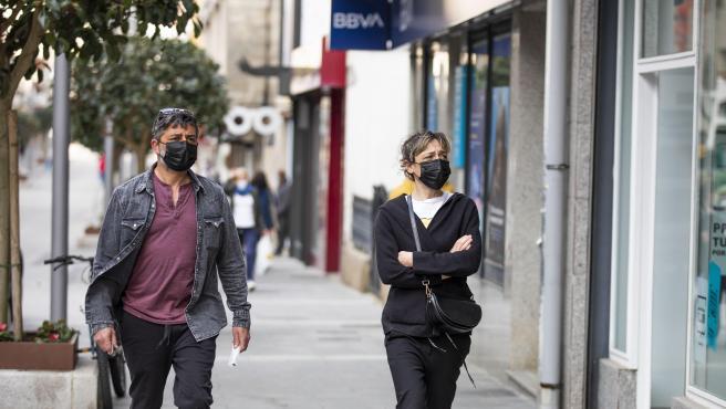 Un hombre y una mujer con mascarilla caminan por una calle de O Grove, en Galicia.