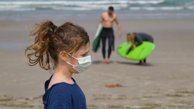 Una niña paseando con mascarilla por la playa