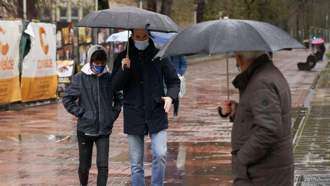 Varias personas se refugian con un paraguas de la lluvia en Vitoria.
