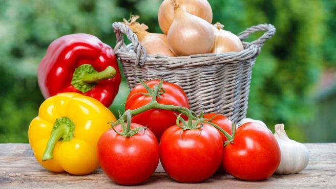 Recolección de tomates, pimientos y cebollas en el huerto.