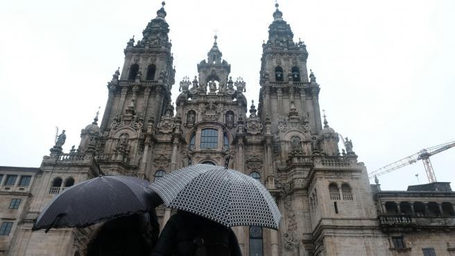 Una pareja observa la catedral de Santiago sin andamios después de varios años de obras.
