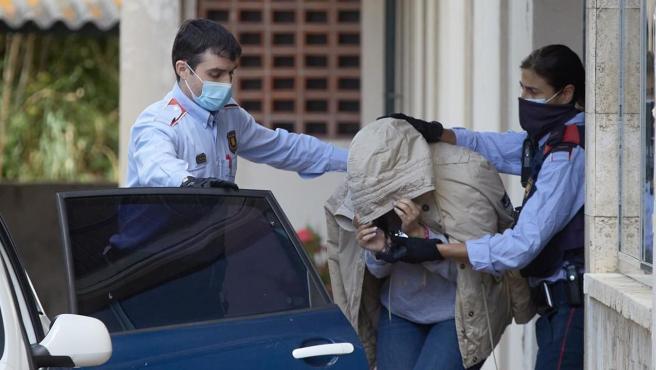 Una persona es conducida por agentes de los Mossos d'Esquadra en Sant Feliu de Guixols (Girona), dentro de una macrooperación policial contra una red acusada de falsificar permisos de conducir.
