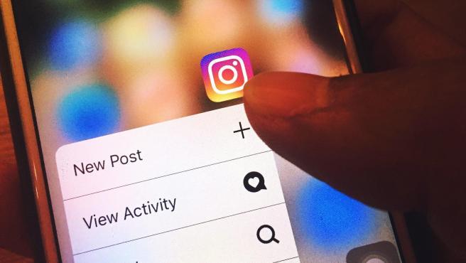 Una persona abriendo la aplicación de Instagram en su móvil.
