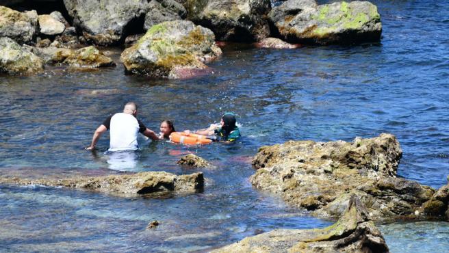 El Grupo Especial de Actividades Subacuáticas (GEAS) de la Guardia Civil rescata a una niña que ha llegado a la playa del Benzú junto a otra mujer, a 17 de mayo de 2021, en Ceuta (España).