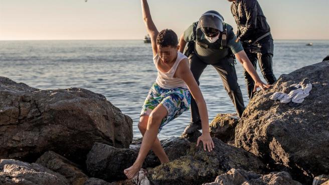 Un menor migrante es seguido por un guardia civil a su llegada este miércoles cerca a la playa ceutí de El Tarajal.