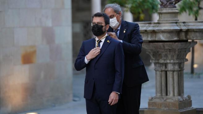 Quim Torra coloca la medalla de presidente de la Generalitat a Pere Aragonès, durante el acto de su toma de posesión.