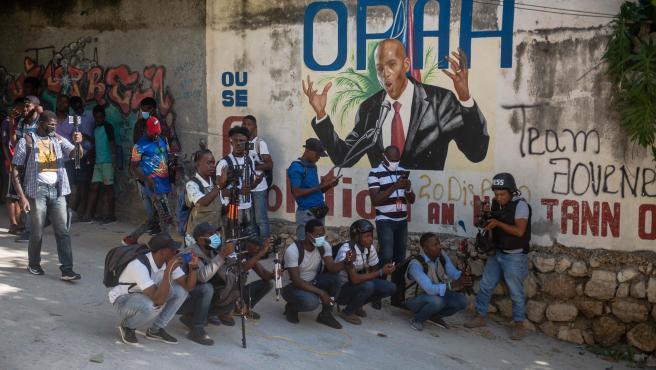 Periodistas junto a un mural con la imagen del asesinado presidente de Haití, Jovenel Moise, en Puerto Príncipe.