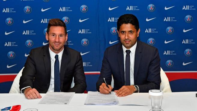 Messi posa sonriente junto al presidente del PSG, Nasser Al-Khelaïfi, tras firmar el contrato con el equipo parisino.