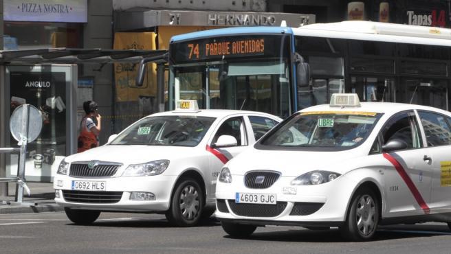 Imagen de archivo de dos taxis circulando por Madrid.