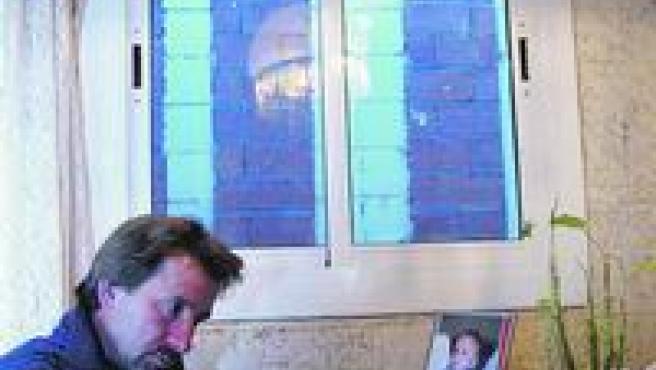 Manuel Brito, en su casa del barrio de Sants, con la ventana tapada por un muro.