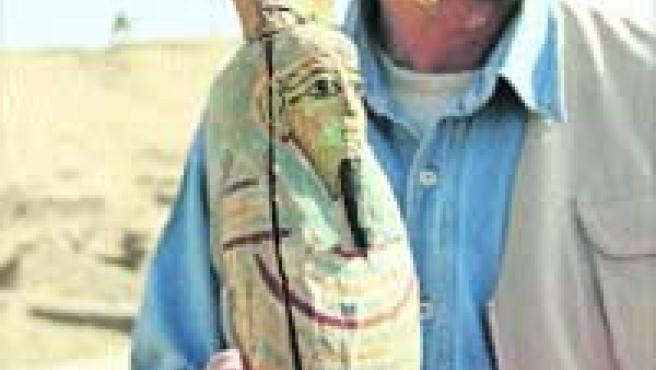 Arriba, un experto sostiene una estatua de Petah Sakar, el dios del cementerio, hallada junto a las tres momias. A la derecha, una lápida que recrea en relieve a una pareja de la corte real faraónica, y una de las tres momias.