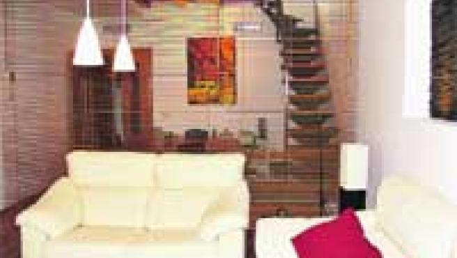 El salón está divivido discretamente en dos ambientes con unas láminas de madera que filtran la luz
