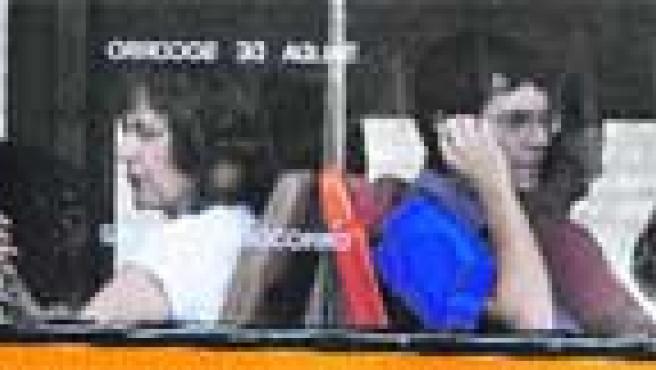 Dos mujeres suplen con el aire de sus abanicos la ausencia de aire acondicionado en el autobús.