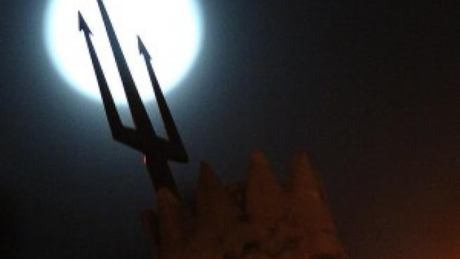 La luna tras la fuente de Neptuno, en Madrid (EFE)