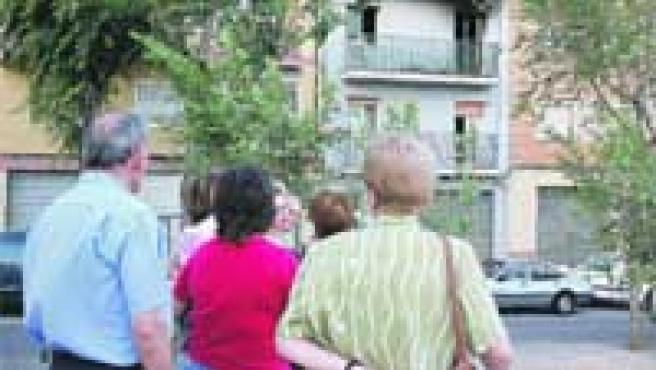 Un grupo de vecinos observan, ayer, el estado en que quedó el segundo piso tras el fuego.