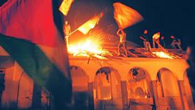Varios palestinos queman un edificio en Gaza (Reuters).