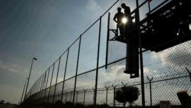 Dos vigilantes hacen guardia en la frontera entre Melilla y Marruecos
