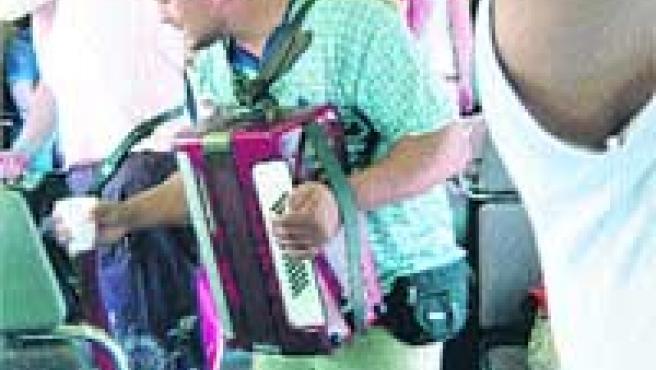 Un músico pide dinero en un vagón de tren de Cercanías.