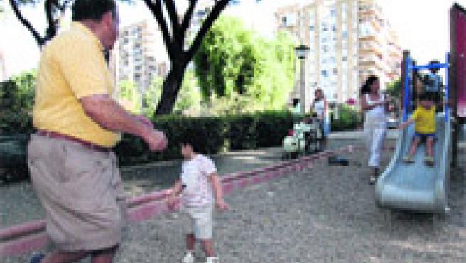 Abuelos y mamás juegan con sus pequeños en los columpios del parque.