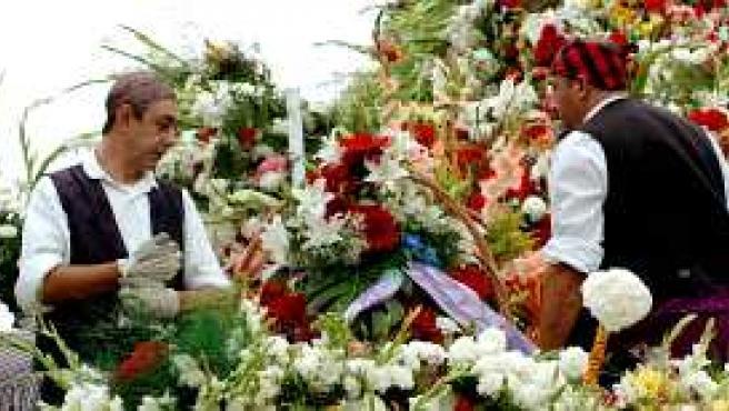Dos mañicos colocan los ramos de flores en el manto de la Virgen (Efe).