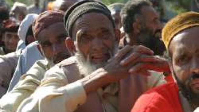 Unos hombres esperan a recibir víveres en Bagh. (Foto: Efe)