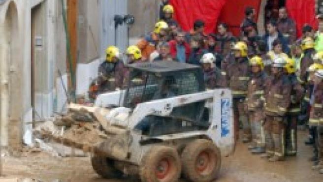 Los bomberos trabajan en el edificio derruído de Piera