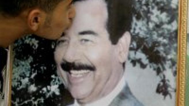 Un hombre jordano besa un poster de Sadam Husein (Reuters)