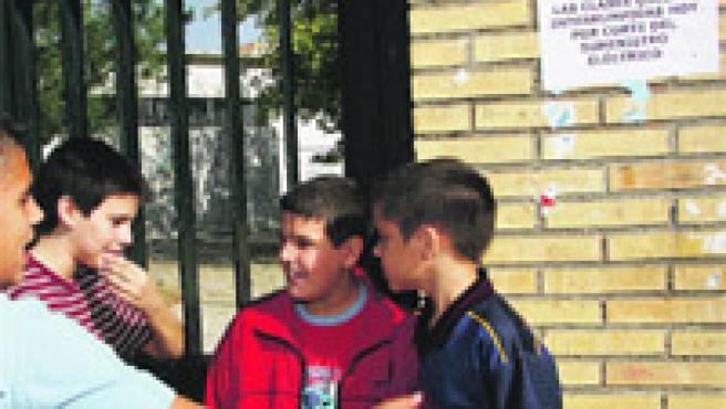Alumnos en la puerta del IES, donde se anuncia la suspensión de las clases por el corte de luz.