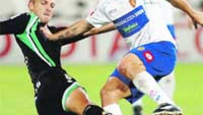 El brasileño Savio disputa un balón con el jugador del Racing Sergio Matabuena.