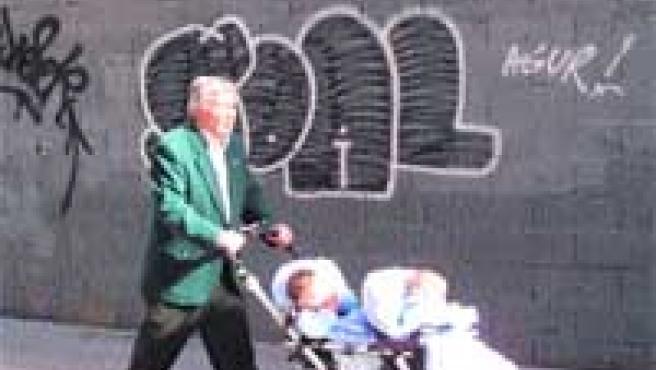 Un señor pasea con dos bebés por la calle Esperanza, frente a un graffiti en un muro.