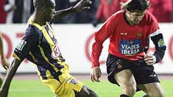 El jugador del RCD Mallorca Jorge González trata de escapar de Luis Amaranto Perea (EFE)