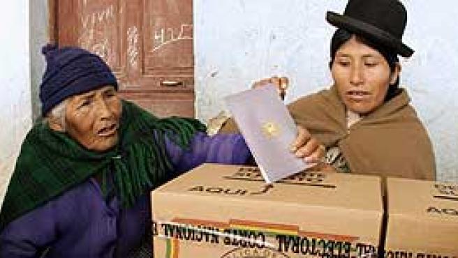 Una mujer boliviana deposita su voto en las cajas de cartón habilitadas al efecto (Reuters)