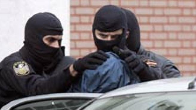 Dos policias meten a un sospechoso en un coche (EFE)
