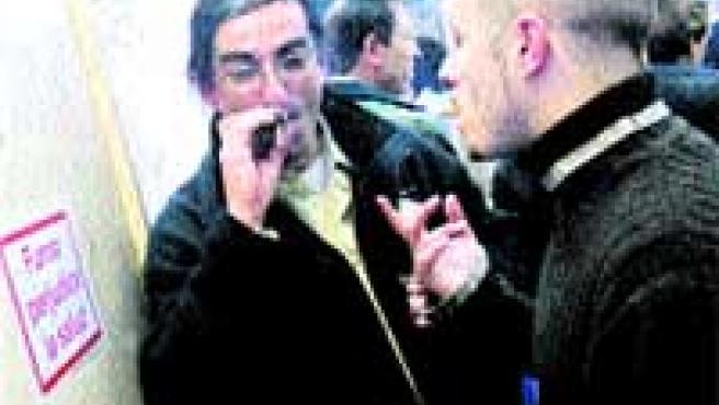 Los fumadores buscan dónde encender un cigarrillo.