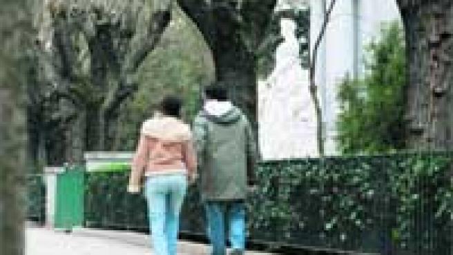 Una pareja, caminando por en el paseo del Pintor Rosales, junto a la estatua de La Chata.