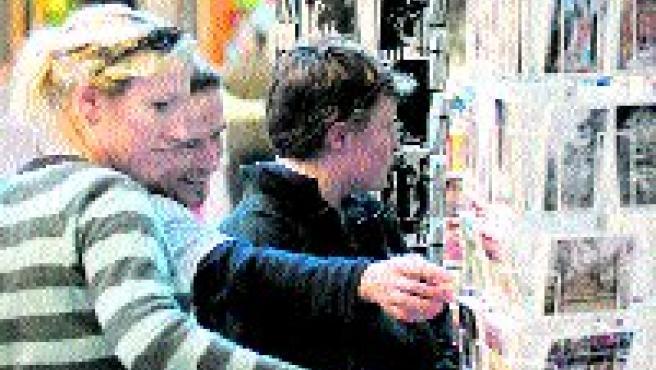 Turistas observan postales de la provincia en la capital.