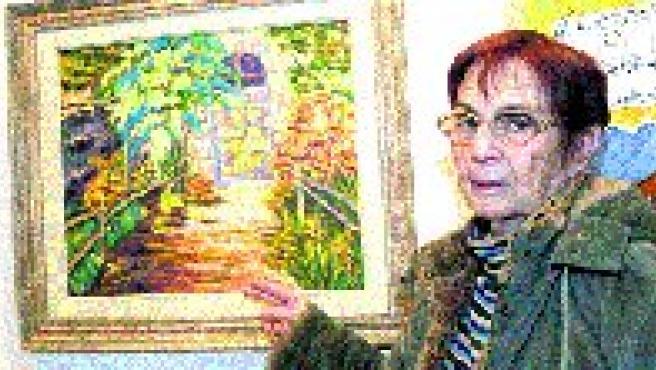 La artista posa junto a uno de sus cuadros.