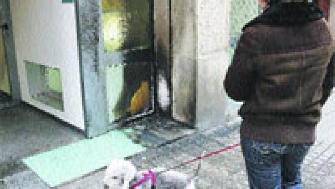 Una joven observando ayer los desperfectos por un fuego en una fachada de la calle Bailén.