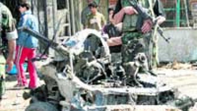Tropas iraquíes custodian los restos de un coche bomba.