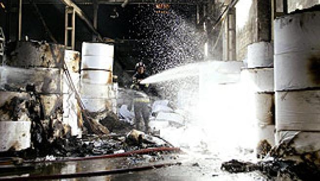 Un bombero apaga el fuego en el interior de la fábrica (Guido Manuilo/Efe).