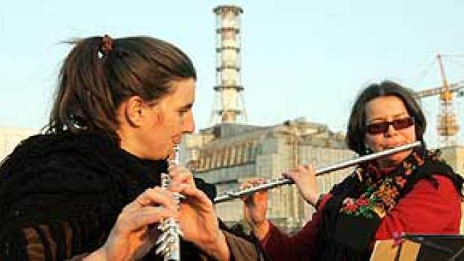 Músicos franceses tocan frente al reactor número 4 en la víspera del aniversario de la catástrofe. (Reuters)