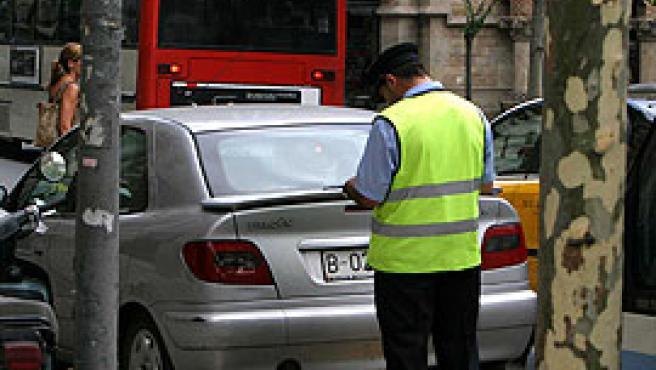 Un agent de la zona blava multa a un cotxe a Barcelona (Arxiu).