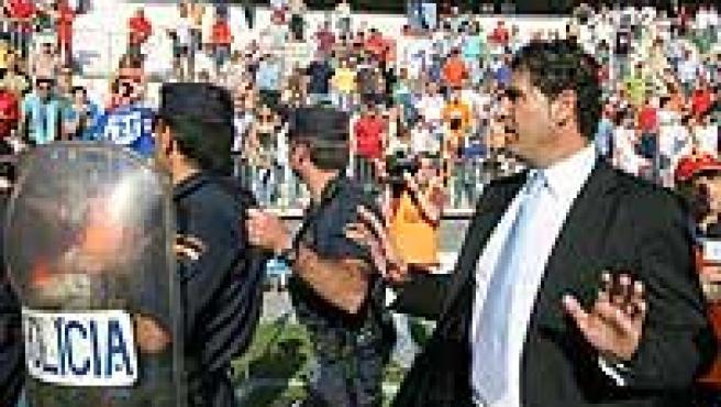 El entrenador del Málaga, Manolo Hierro (i) entra protegido por agentes de la Policía al túnel de vestuarios. (Efe/Paco Rodríguez)