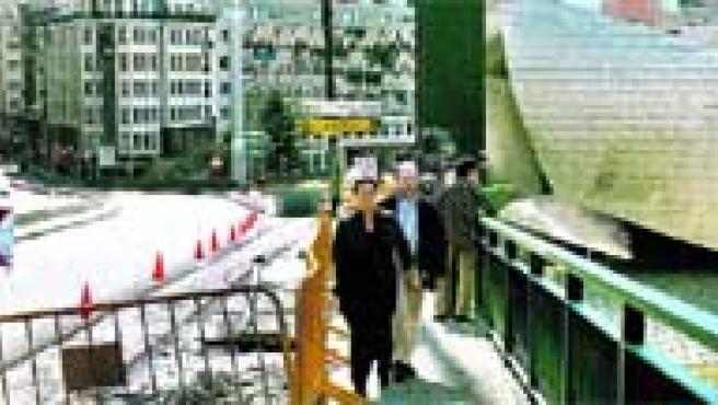 Varios peatones pasan por una de las aceras del puente de La Salve, mientras se desarrollan las obras de transformación en bulevar.